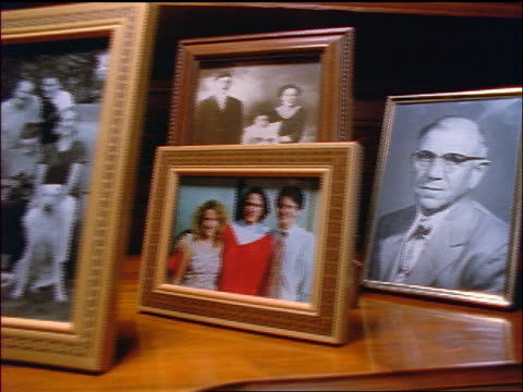 close up dolly shot picture frames with family photos on shelf