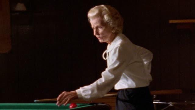 Close up elderly woman playing pool / medium shot cueing stick / shooting cue ball / pan cue ball / San Francisco