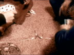 1971 Close up feet of four young people sitting on floor holding playing cards and grabbing spoons/ pan man laughing/ California/ AUDIO
