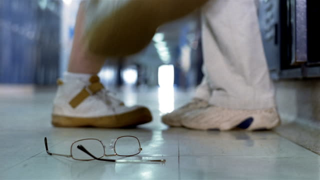 Close up feet of school bully stomping on boy's glasses in hallway