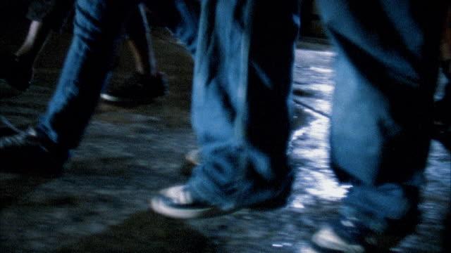 Close up feet walking on wet street at night