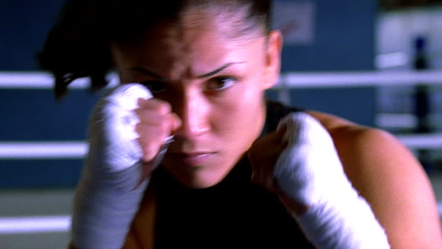 close up female boxer in boxing ring ducking + shadow boxing toward camera