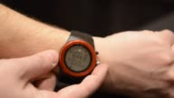 Close up female finger operating smart watch calorie feature on wrist at the Consumer Electronics Show in Las Vegas Close up male hands wearing smart...