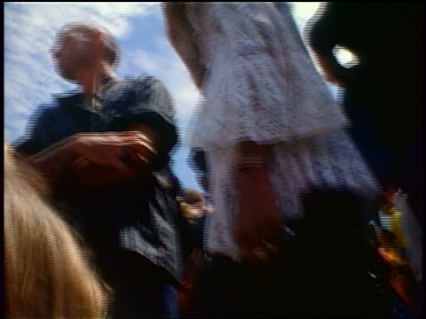 1968 close up female hippie wearing lace shirt standing in crowd at outdoor concert / Tapia Park CA