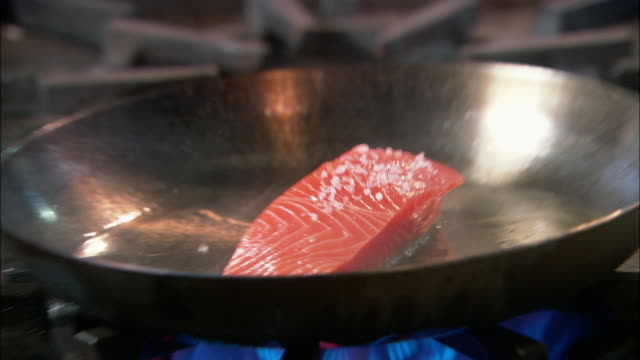 Close up fillet of salmon being cooked in frying pan / Auckland, New Zealand