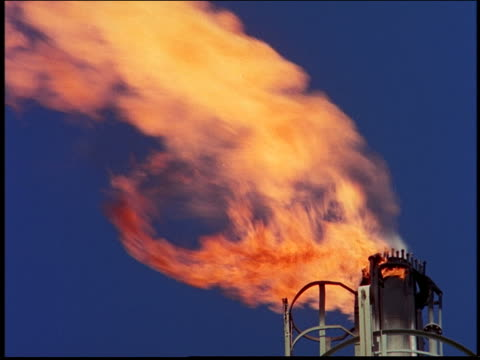 close up fire pouring out of smokestack in blue sky / oil refinery / Brazil