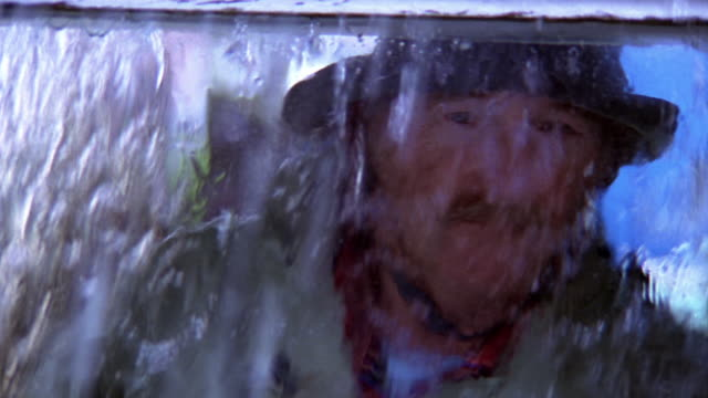 Close up fisherman in hat and raincoat looking out window (shot from outdoors) in heavy rain / Nova Scotia
