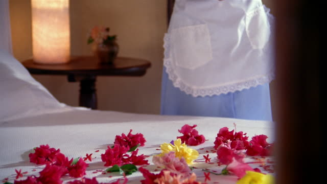 Close up flower petals on bed / zoom out dolly shot housekeeper arranging flowers on bed in hotel room