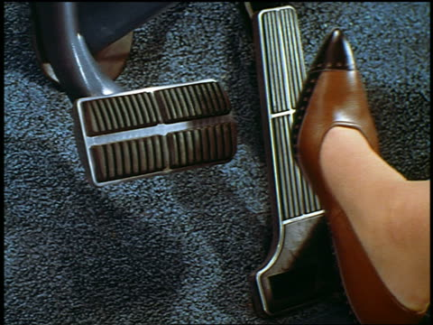 1962 close up foot of woman in high heels stepping from gas pedal to brake pedal / industrial