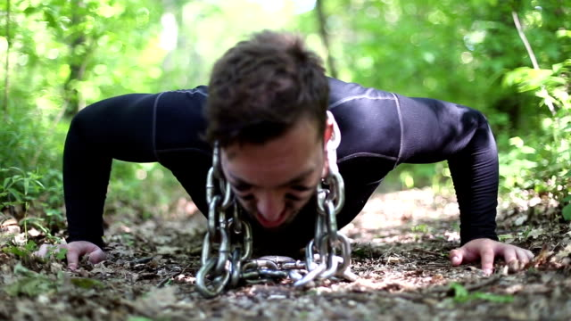 Close up footage of a man doing push ups with chains around his neck