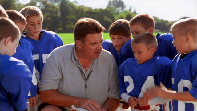 Close up football coach instructing group of young boys in football uniforms / performing high five