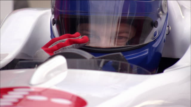 Close up Formula One race car driver lowering visor on his helmet and gripping steering wheel