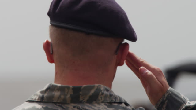 Close up from the back of a US military soldier wearing beret, stands at attention and salutes.