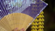 Close up geisha woman outdoors moving fan across eyes / Japan