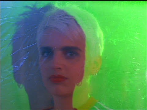 close up Gen X woman standing behind plastic + spray painting it red