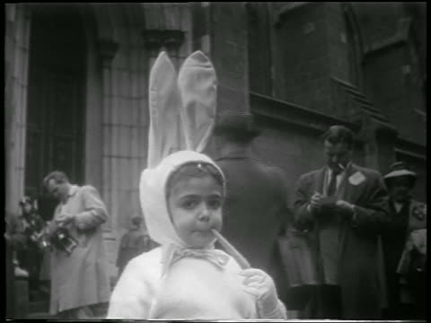 B/W 1952 close up girl in bunny costume with carrot in mouth looking at camera outdoors / Easter / NYC