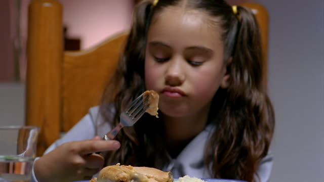 Close up girl picking at food with fork and frowning during meal / Mexico City