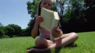 Close up girl showing book to CAM / low angle medium shot young girl sitting in grass and reading book with trees in background