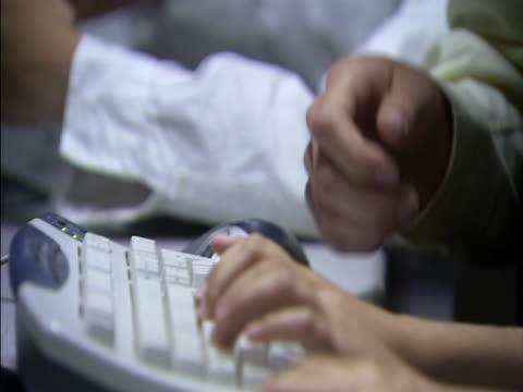 Close up girl's and teacher's hands on computer keyboard/ tilt up teacher talking to girl/ London, England