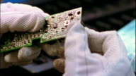 Close up gloved hands examining computer chip board / soldering computer chip board