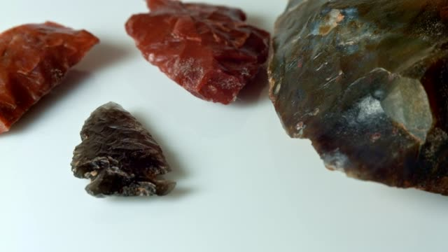 Close up group native american artifacts hand axe ax red obsidian arrowhead jasper chert paiute indian stone tool in dirt from Oregon great basin desert on white