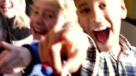HIGH CONTRAST close up PAN group of children laughing + pointing at camera