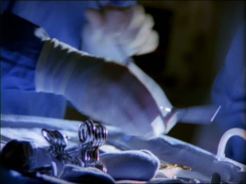 Close up hand checking drip rate in operating room / pan surgical instrument tray to female surgeon's face