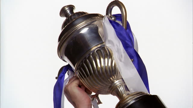 Close up hand holding trophy cup w/ribbons against white background