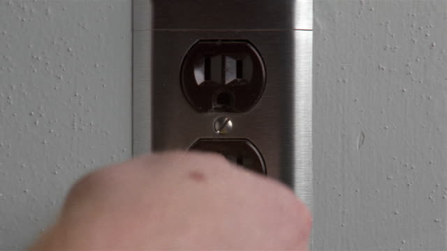 Close up hand inserting yellow plug into black outlet and pulling it out again