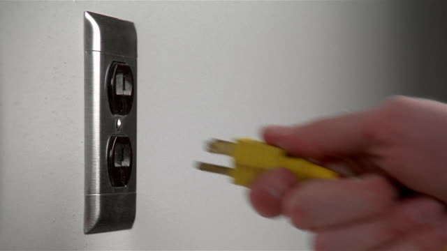 Close up hand inserting yellow plug into wall outlet and pulling it out again