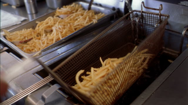 Close up hand lifting basket of french fries / drying and seasoning w/salt on towel