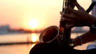 Close up hand of saxophone players at sunset