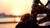 Nahaufnahme der hand mit Saxophon-Spieler bei Sonnenuntergang