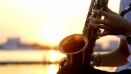 Primo piano della mano giocatori Sassofono con tramonto