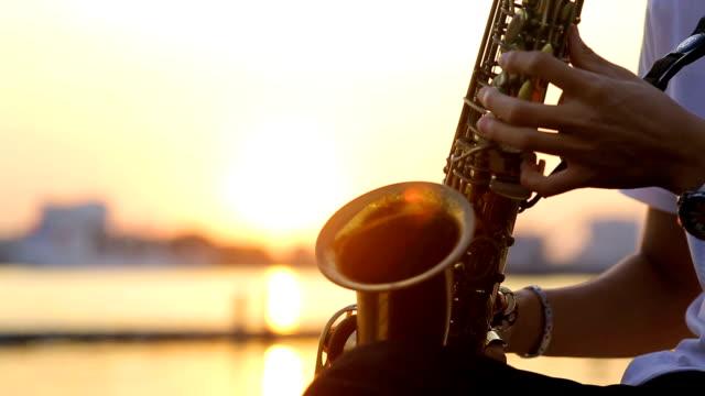 Nahaufnahme der hand mit Saxophon-Spieler mit Sonnenuntergang