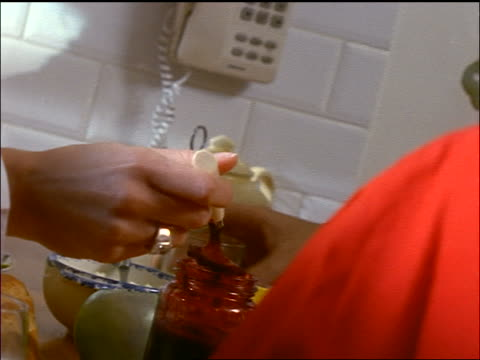 close up hand of woman spreading jam on toast with spoon in kitchen