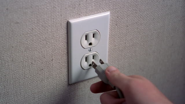 Close up hand plugging three prong cord into electric socket