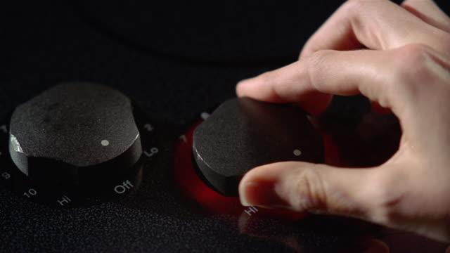 Close up hand turning on stove knob, illuminating it red