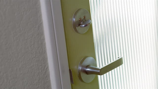 Close up hand unlocking and opening door with glass panel from inside of room