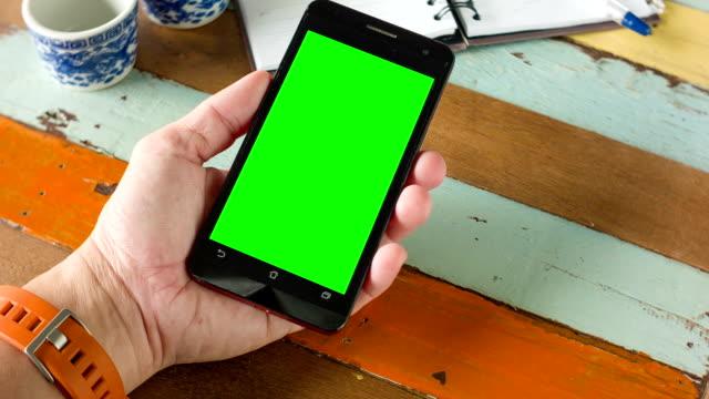 Nahaufnahme der hand mit Smartphone mit leeren grünen Bildschirm für chroma key