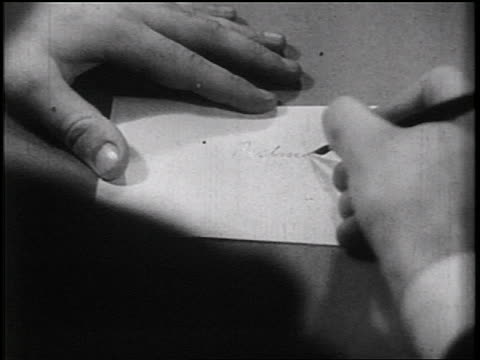 B/W 1936 close up hand writing 'Postmaster' on envelope / documentary