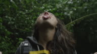 Close up handheld shot of woman catching rain with tongue / Arenal, Costa Rica