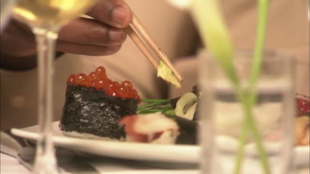Close Up hand-held tilt-down tilt-up - A restaurant patron selects a piece of sushi with chopsticks