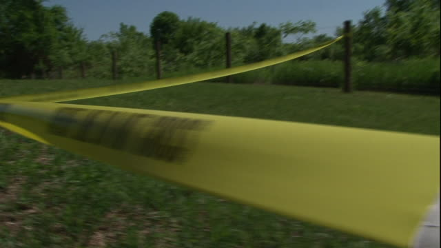 Close Up hand-held tracking-right - A sheriff stretches crime scene tape across a cemetery lawn. / USA