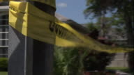 Close Up hand-held tracking-right - Crime scene tape blows in the breeze around a house. / USA