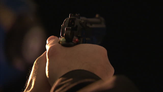 Close Up hand-held - Two hands aim a gun, then pull the trigger.