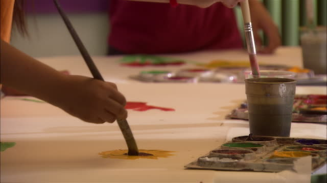 Close up hands and paintbrushes painting on table/ tilt up girls painting in art class/ pan flower arrangement/ London
