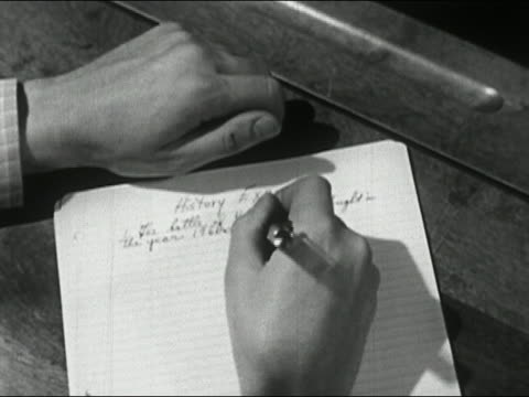 1950 Close up hands and paper of boy taking history exam / opens left hand to reveal cheat sheet / AUDIO