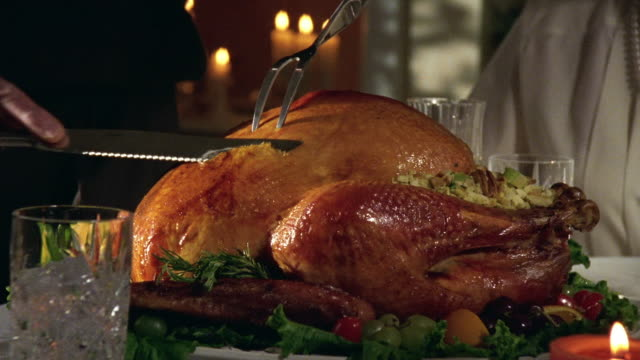 Close up hands carving roast turkey on platter on dining room table