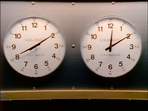 close up hands move on two international clocks (Sao Paulo + Strasbourg)